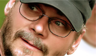 A Close Up Of A Man Wearing A Hat And Glasses